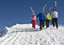 A group of skiers seeking adventure on their way to the top of the Summit to ski down some pristine virgin snow on a beautiful sunny day